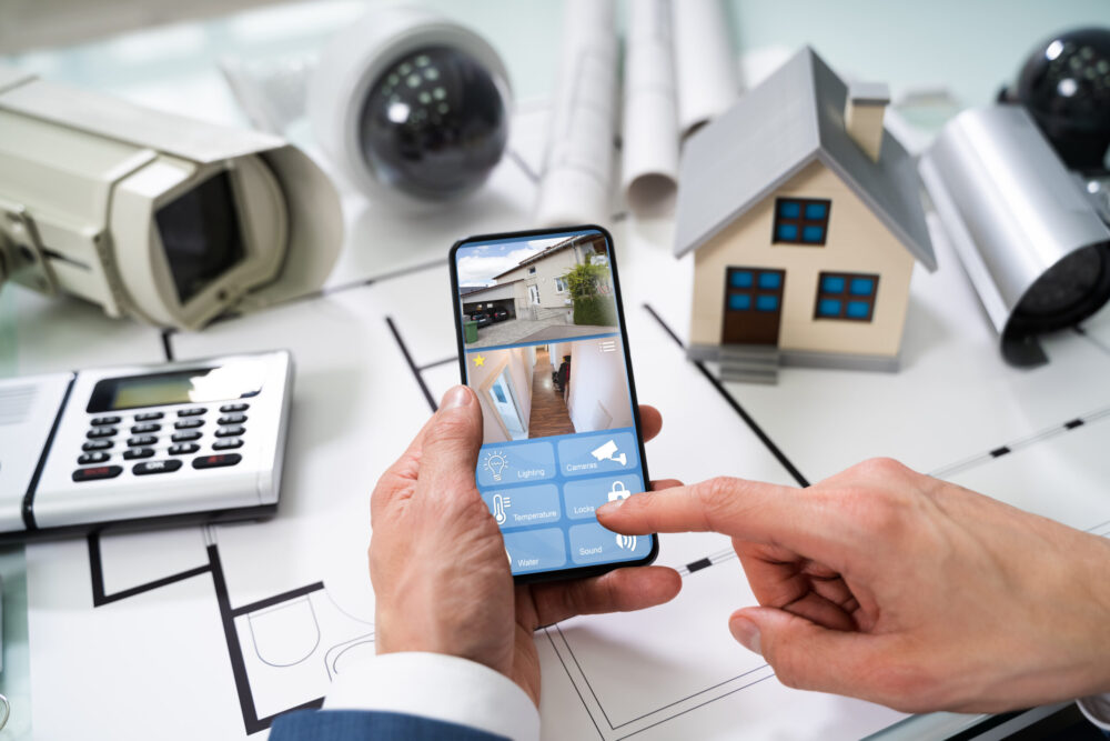 home monitoring Phoenix Home Security Systems Person Hand Using Home Security System On Mobilephone